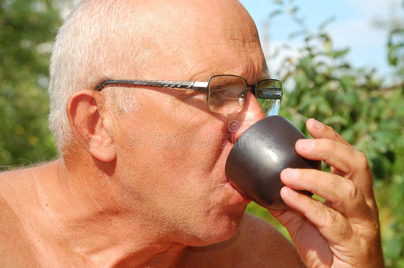 Trinkender Tee des älteren Mannes im Freien lizenzfreie stockfotos