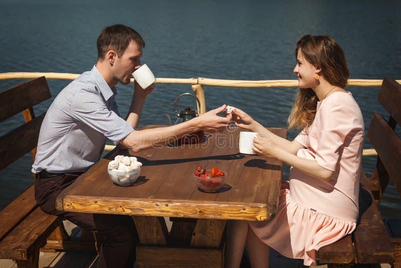 Trinkender Tee des glücklichen Paars draußen stockfoto