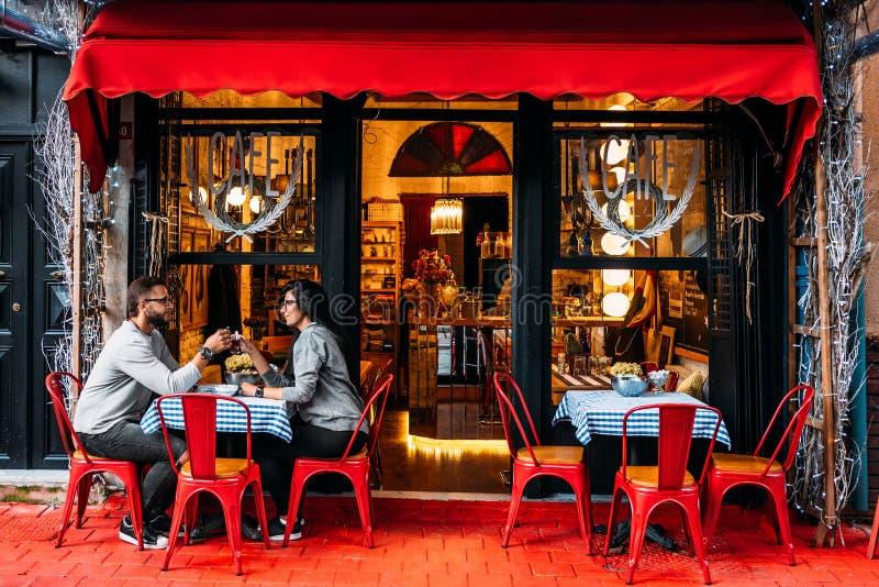 Trinkender Tee des glücklichen Paars in einem Straßencafé Paare in der Liebe in einem Caf? Trinkender Tee des Mannes und der Frau lizenzfreies stockbild