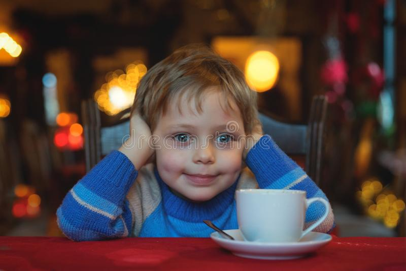 Trinkender Tee des 8-jährigen Jungen im Café mit Weihnachtslichtern lizenzfreie stockfotos