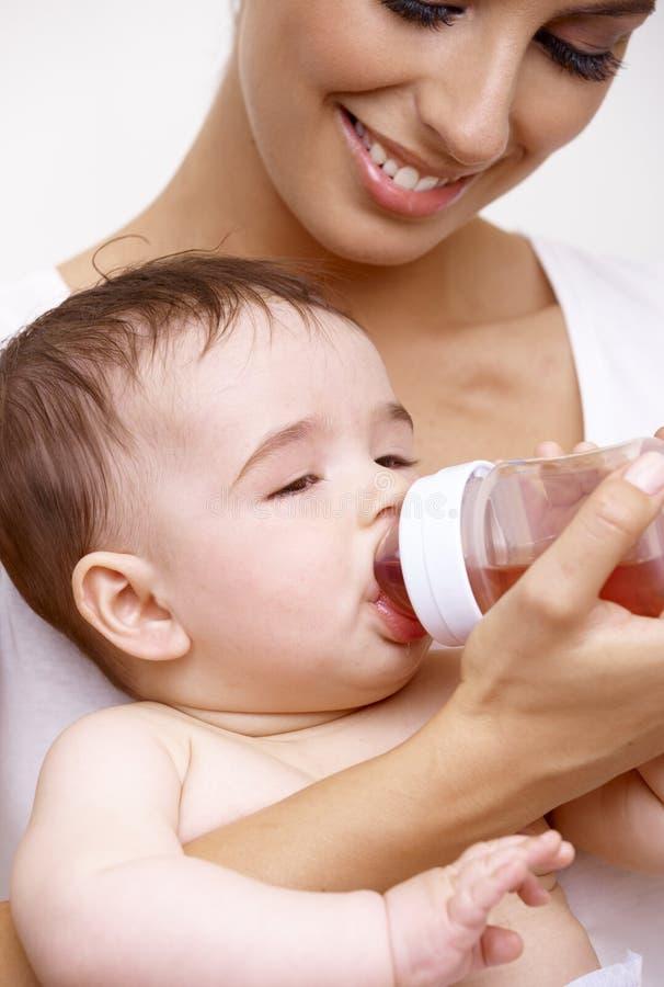 Trinkender Tee des schläfrigen Babys von der Saugflasche stockfoto