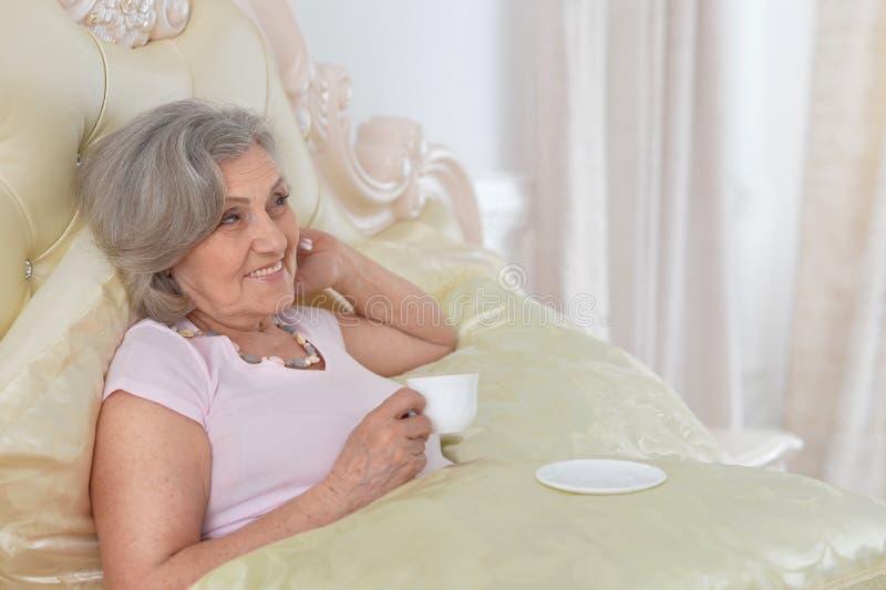Trinkender Tee Seniour-Frau zu Hause lizenzfreies stockfoto