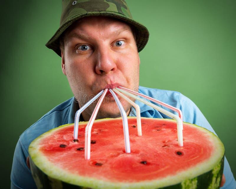 Trinkender Wassermelonensaft des Landwirts lizenzfreie stockfotos