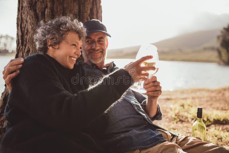 Trinkender Wein der älteren Paare am Campingplatz stockfotos
