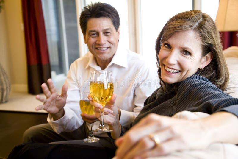 Trinkender Wein der fälligen Paare zusammen auf Couch stockbilder