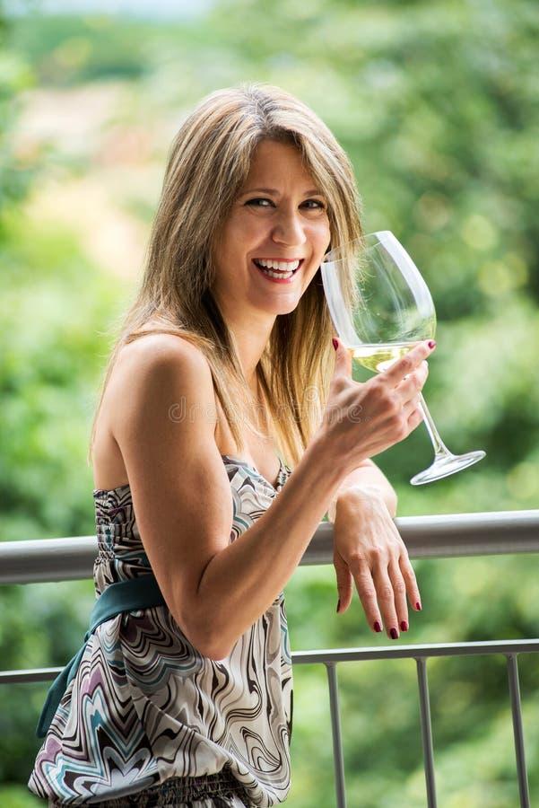 Trinkender Wein der glücklichen Frau und Feiern stockfotos