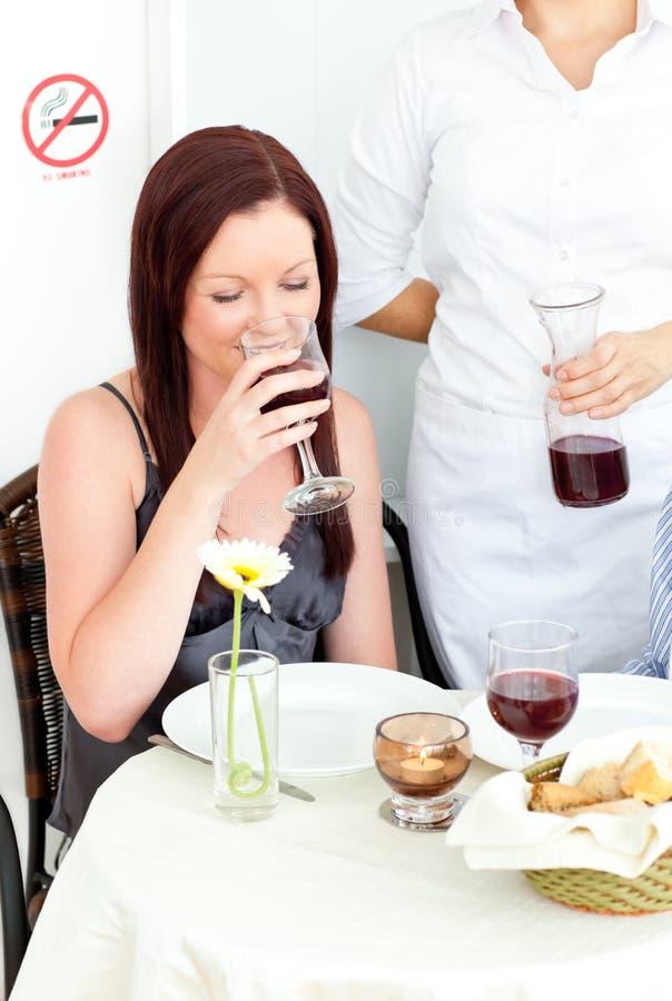 Trinkender Wein der glücklichen Freundin an der Gaststätte lizenzfreies stockbild