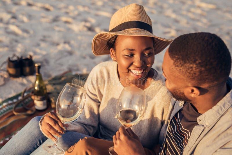 Trinkender Wein der glücklichen jungen afrikanischen Paare zusammen am Strand stockbilder