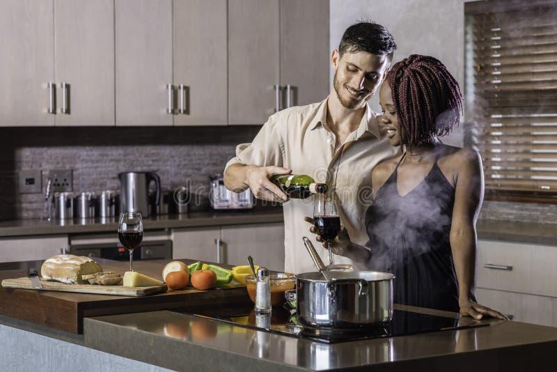 Trinkender Wein der glücklichen jungen Mischrassepaare, der Abendessen in der Küche kocht stockfotografie