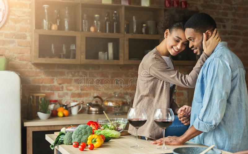 Trinkender Wein der liebevollen Afroamerikanerpaare in der Küche stockfotos