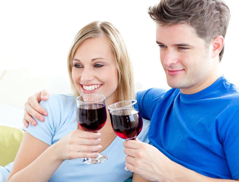 Trinkender Wein der liebevollen Paare auf einem Sofa lizenzfreie stockfotografie