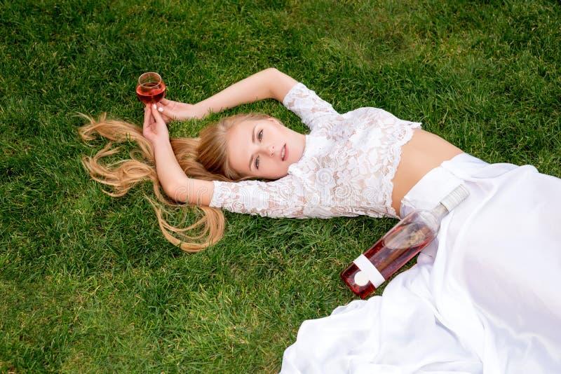 Trinkender Wein der Schönheit draußen Porträt der jungen blonden Schönheit in den Weinbergen, die Spaß, ein Glas von genießend ha stockbild