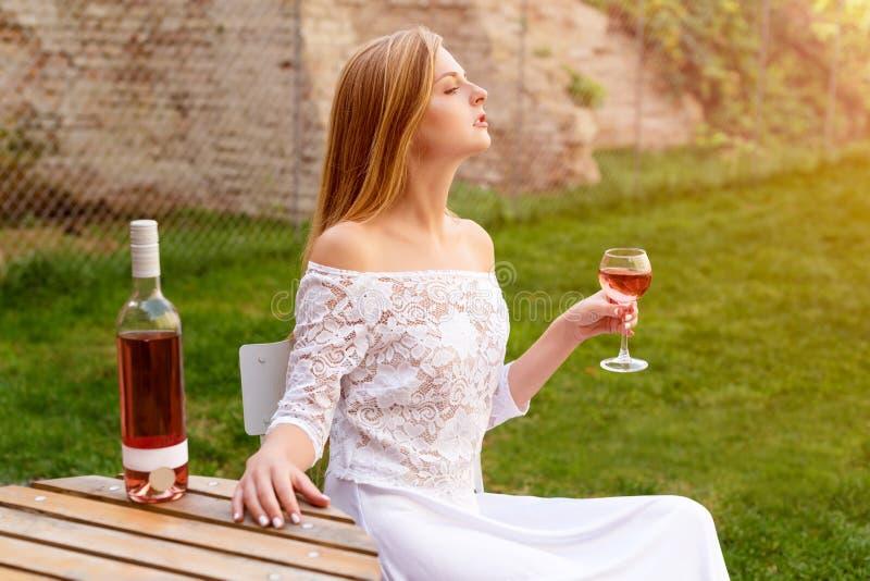 Trinkender Wein der Schönheit im Freiencafé Porträt der jungen blonden Schönheit in den Weinbergen, die Spaß, a genießend haben stockfotos