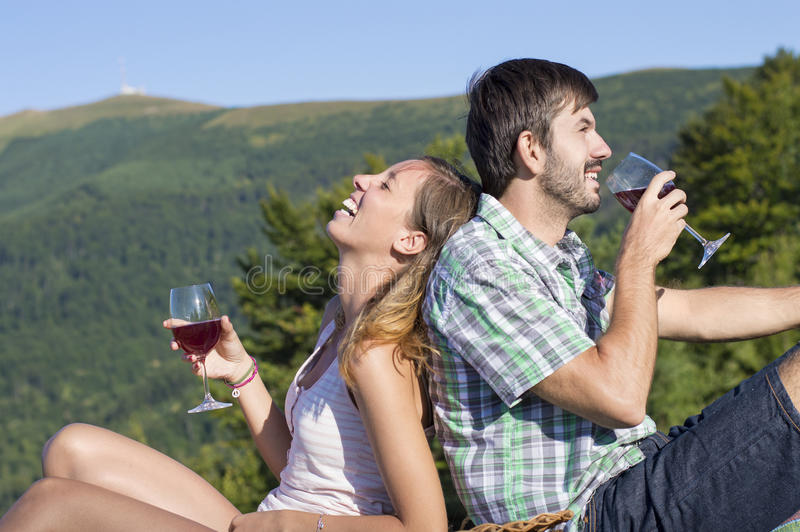 Trinkender Wein des jungen glücklichen Paars auf einer wandernden Reise am viewpoi lizenzfreie stockfotografie