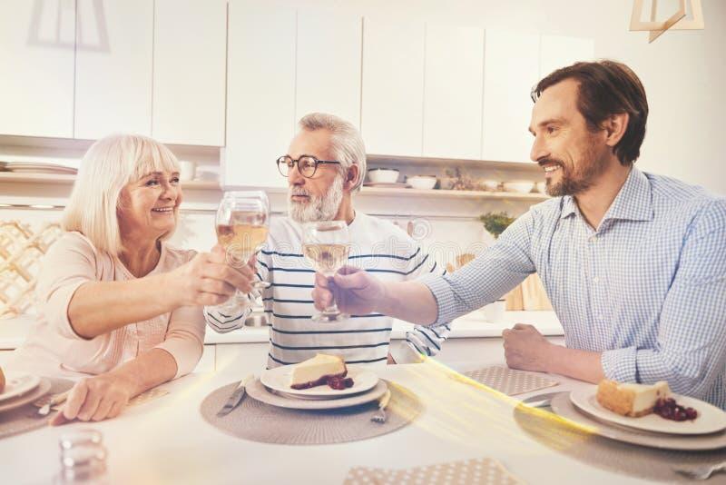 Trinkender Wein des positiven erwachsenen Mannes mit seinen gealterten Eltern lizenzfreie stockfotografie