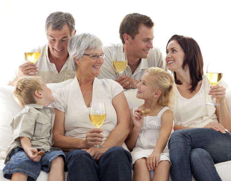 Trinkender Wein und Kinder der Familie, die Biskuite essen stockfoto