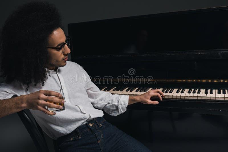 trinkender Whisky des hübschen jungen Musikers und spielen Klavier stockfoto