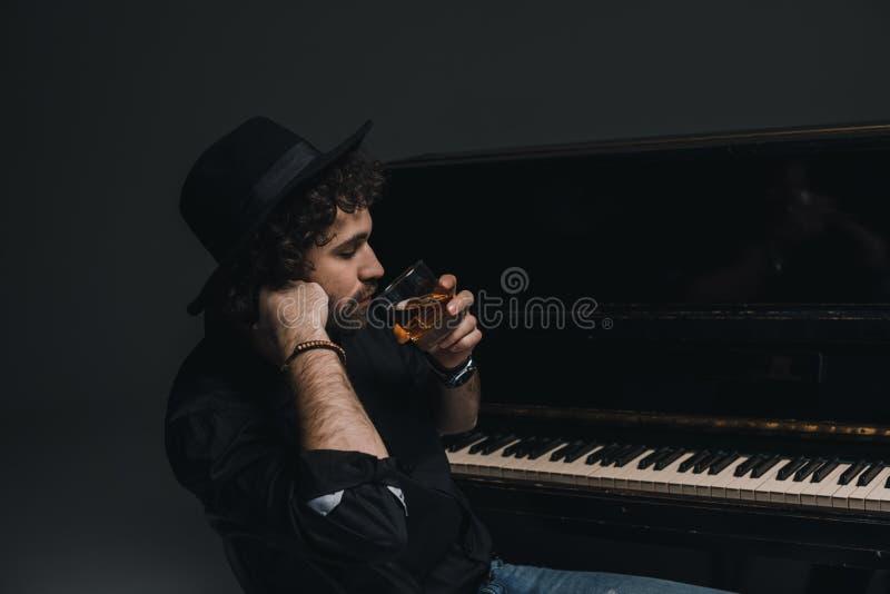trinkender Whisky des hübschen Musikers nahe Klavier lizenzfreie stockfotografie