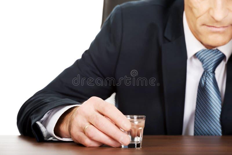 Trinkender Wodka des überarbeiteten Mannes im Büro stockfoto