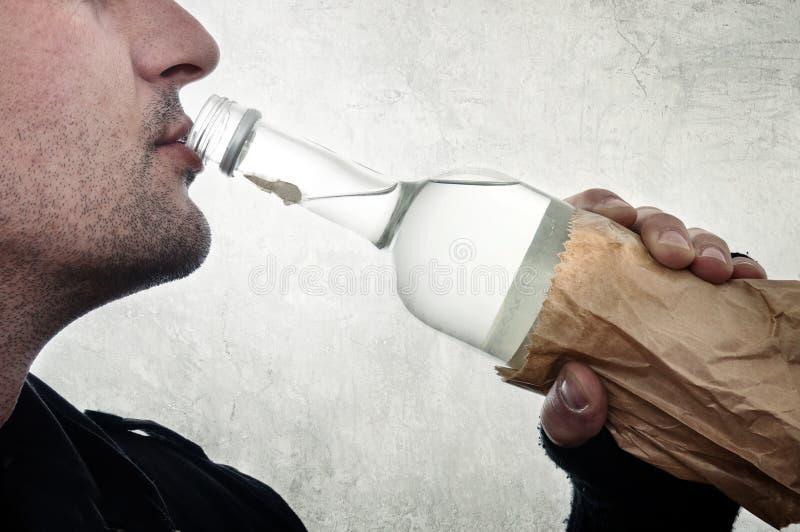 Trinkender Wodka des Mannes von der Flasche lizenzfreies stockbild