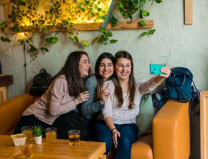 Trinkendes Bier der glücklichen Freundgruppe und selfie am Brauereibarrestaurant nehmen stockfotografie