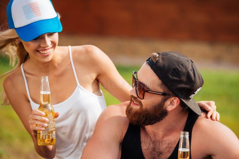 Trinkendes Bier der glücklichen jungen Paare draußen im Sommer stockfoto