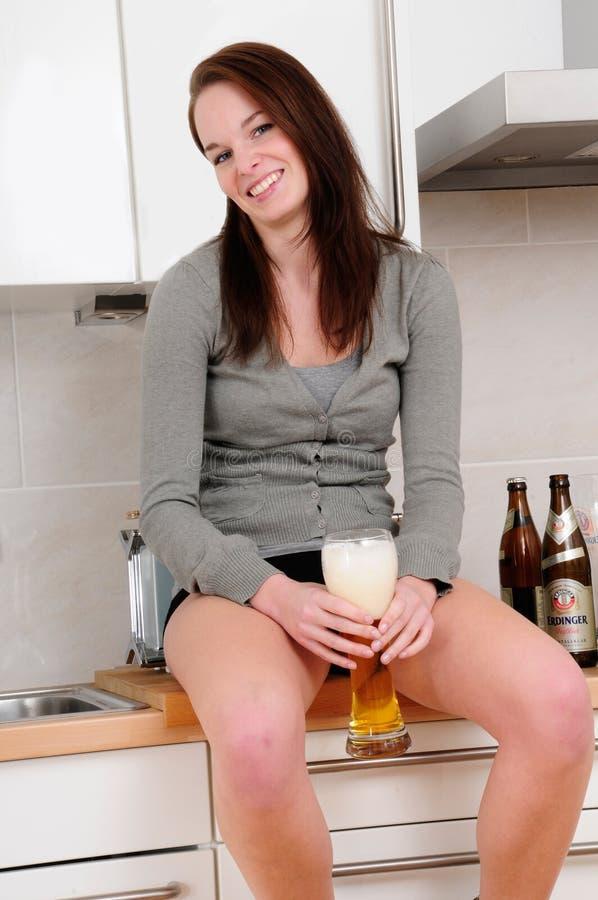 Trinkendes Bier der jungen Frau stockfoto
