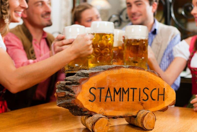 Trinkendes Bier der Leute im bayerischen Pub stockbild