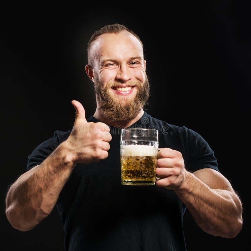 Trinkendes Bier des bärtigen Mannes von einem Bierkrug über schwarzem Hintergrund lizenzfreies stockfoto