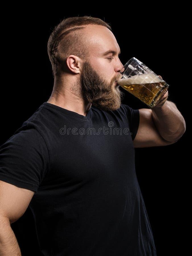 Trinkendes Bier des bärtigen Mannes von einem Bierkrug über schwarzem Hintergrund lizenzfreie stockfotografie