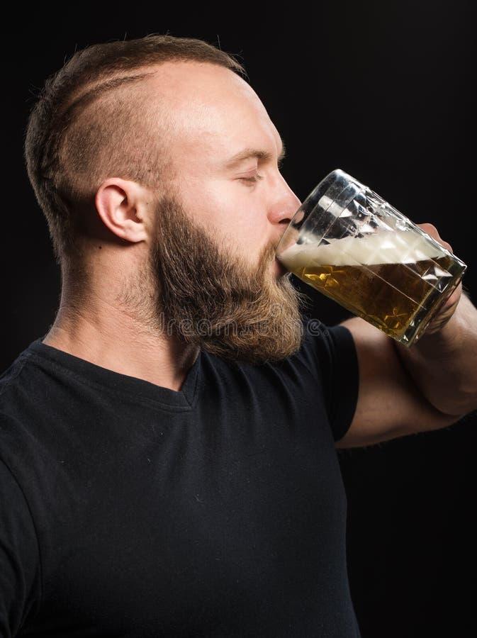 Trinkendes Bier des bärtigen Mannes von einem Bierkrug über schwarzem Hintergrund stockfoto