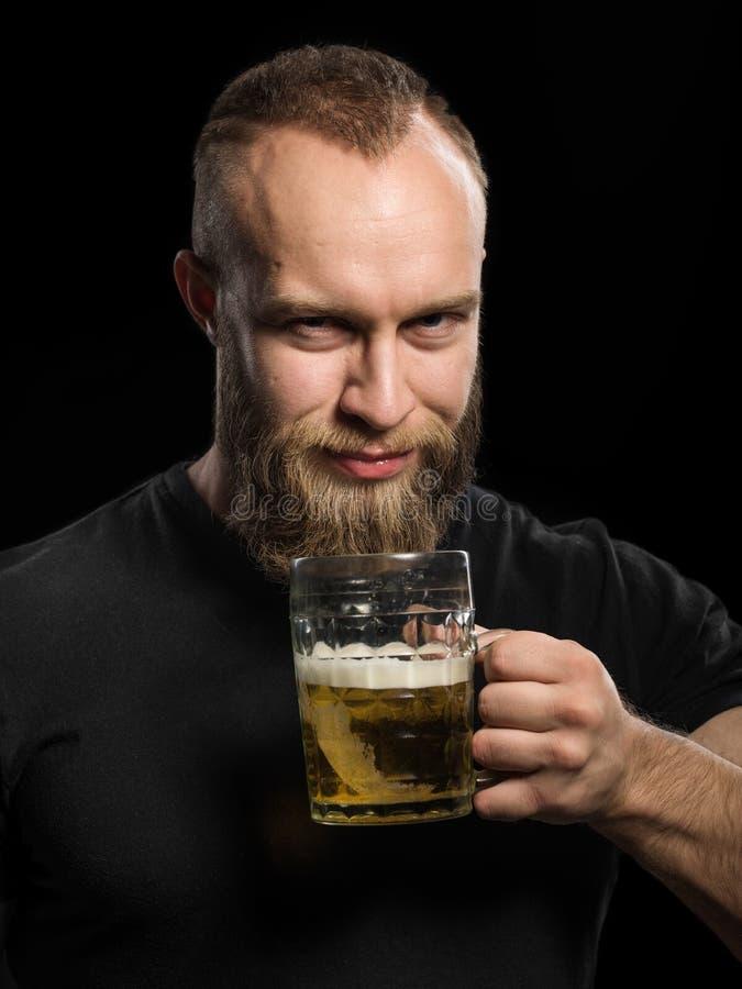 Trinkendes Bier des bärtigen Mannes von einem Bierkrug über schwarzem Hintergrund stockfotos