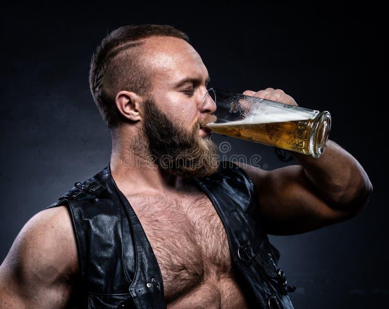 Trinkendes Bier des bärtigen Mannes von einem Bierkrug stockfotos