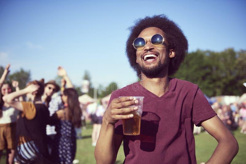 Trinkendes Bier des glücklichen afrikanischen Mannes im Festival stockbild