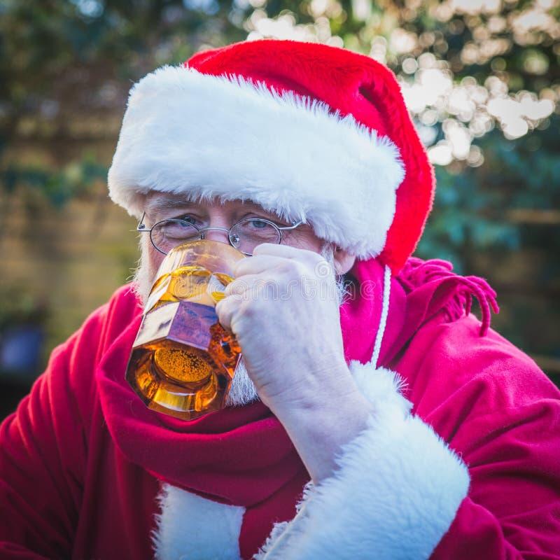 Trinkendes Bier Santa Clauss und Betrachten der Kamera Beifall Christm stockfoto