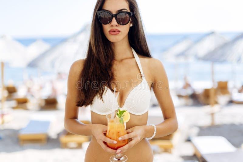 Trinkendes Cocktail der erstaunlichen Frau auf Strand stockbilder