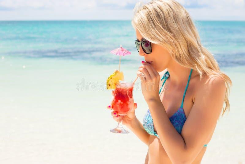 Trinkendes Cocktail der Frau auf dem Strand stockfotos