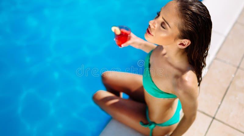 Trinkendes Cocktail der Sch?nheit und Ein Sonnenbad nehmen am Pool stockfotos