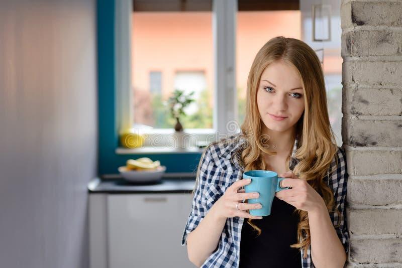 Trinkendes coffe oder Tee der schönen blauäugigen blonden Frau von der Schale stockfotos