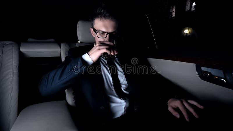 Trinkendes Exekutivgetränk auf Rücksitz des Autos, Heimweg nach hartem beschäftigtem Tag stockfotografie