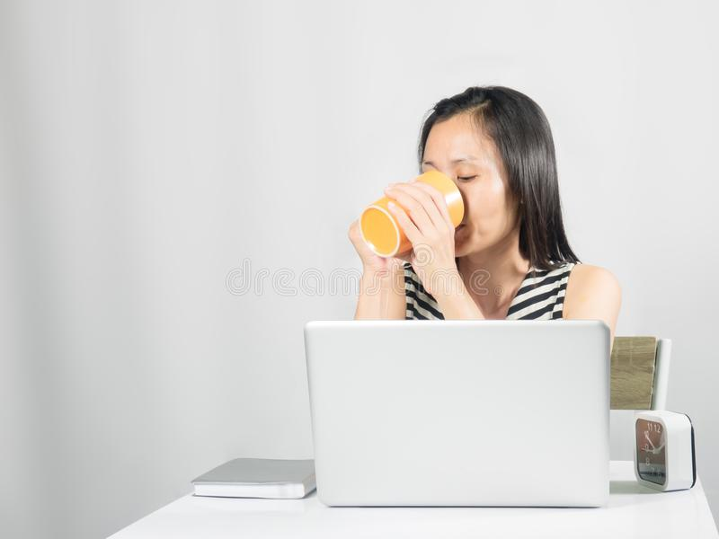 Trinkendes Getränk der netten Frau auf Arbeitsschreibtisch stockbilder