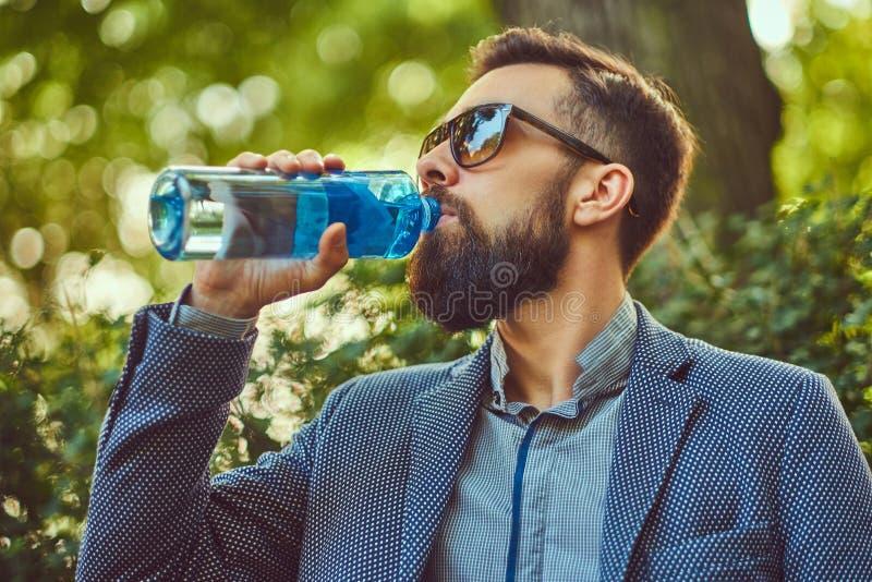 Trinkendes kaltes Wasser des bärtigen männlichen Mannes draußen, sitzend auf einer Bank in einem Stadtpark stockbild