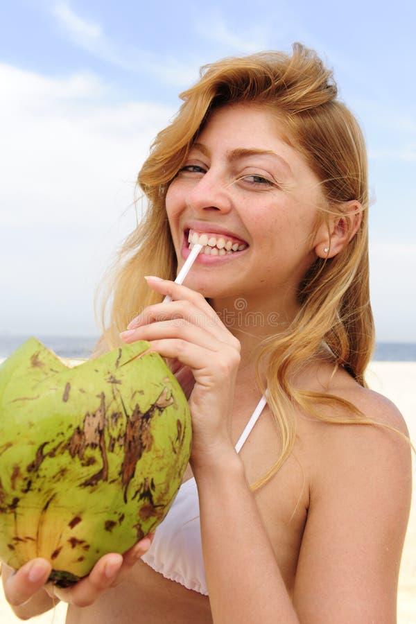 Trinkendes Kokosnusswasser der durstigen Frau auf dem Strand lizenzfreies stockfoto