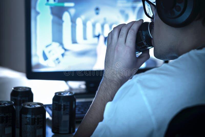 Trinkendes Soda des Kerls und spielen Videospiel oder aufpassender on-line-Livestrom Zu viel Energiegetränk Viele leeren Dosen Ko lizenzfreies stockbild