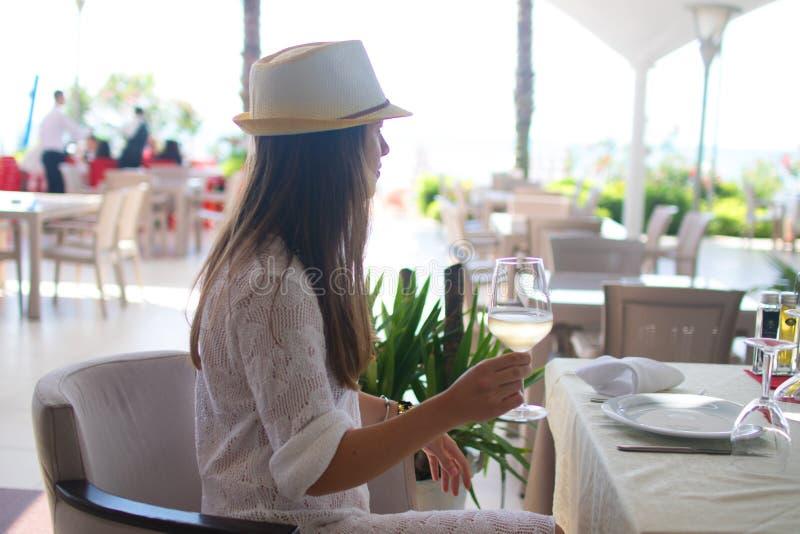 Trinkendes Weißwein der jungen Frau auf Terrasse der im Freien, die an vom Mittelmeer aufpasst Frau in den weißen sundress auf So stockbilder