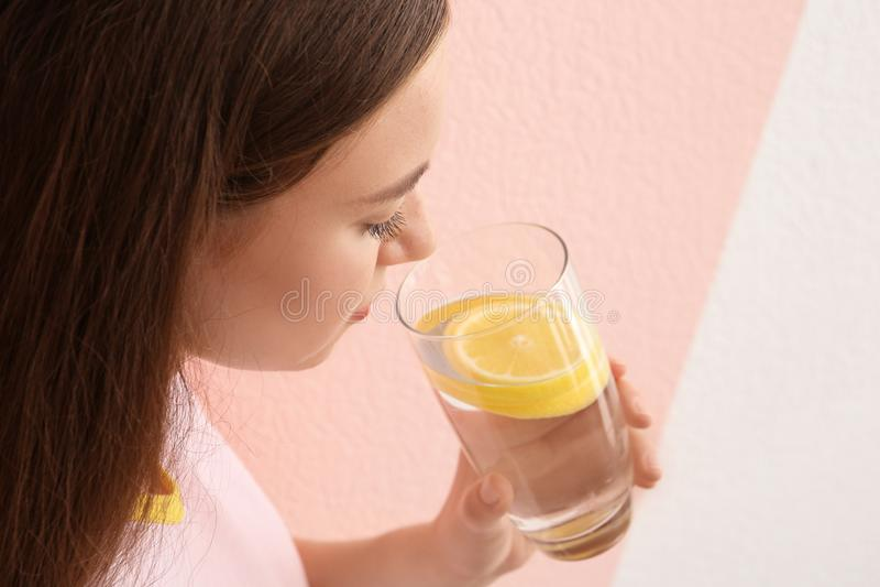 Trinkendes Zitronenwasser der jungen Frau lizenzfreie stockfotografie