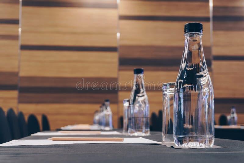 Trinkgläser, Plastikwasserflaschen, Bleistifte und Papiere stockfotografie
