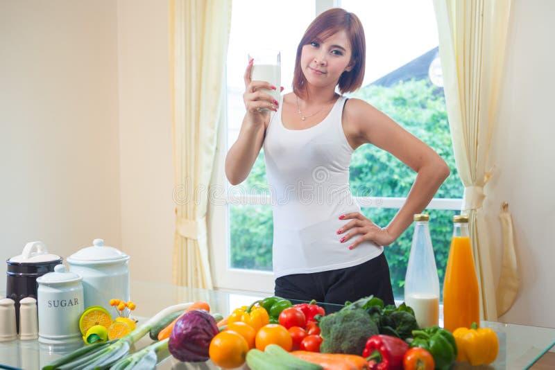 Trinkmilch der jungen asiatischen Frau lizenzfreie stockbilder