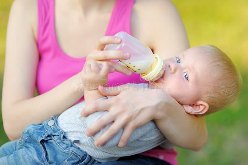 Trinkmilch des Babys von der Flasche in den Mutterhänden lizenzfreies stockbild