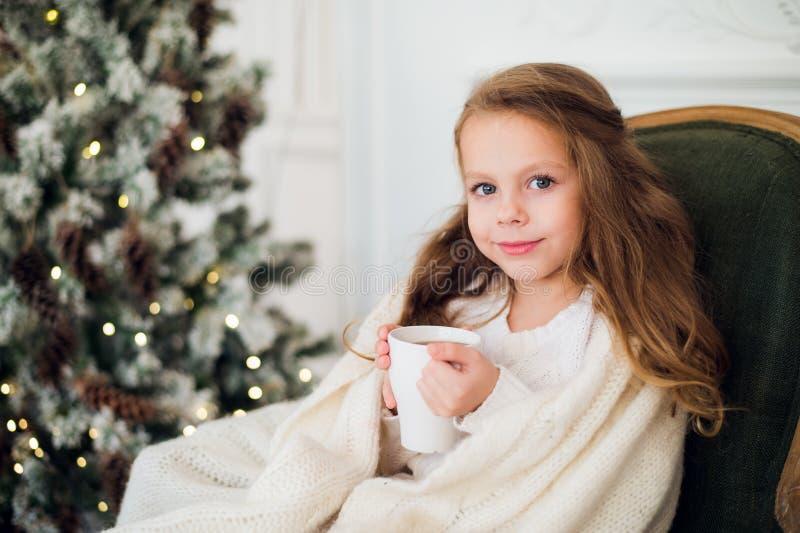 Trinkmilch des kleinen Mädchens nahe Weihnachtsbaum am Morgen zu Hause stockfoto